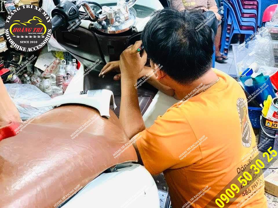 Nhân viên đang tháo dàn áo gắn smartkey cho PCX 2011