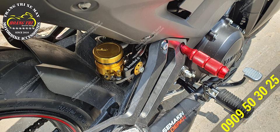Binh dầu AEM màu vàng nổi bật trên nền đen của xe