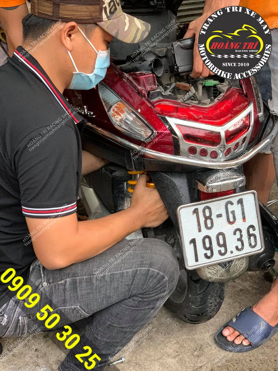 Nhân viên đang lắp đặt phuộc bình dầu Ohlins cho xe Grande