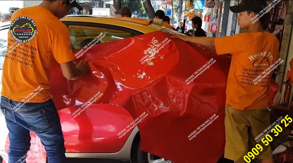 Nhân viên Hoàng Trí Racing shop cắt keo canh dán lên xe