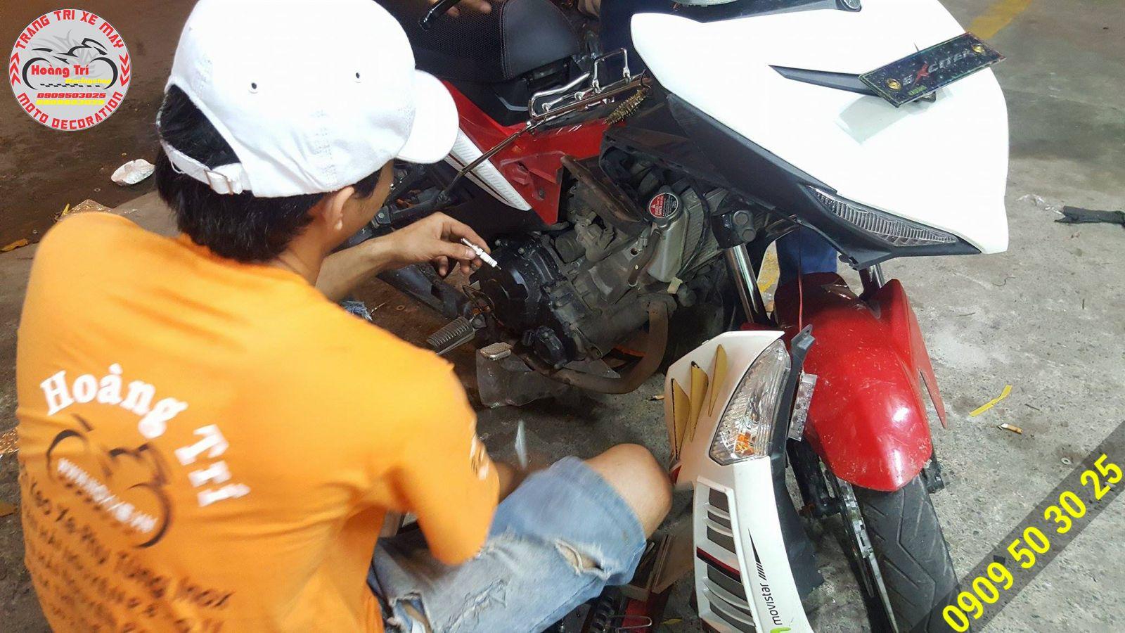 Nhân viên Hoàng Trí Racing Shop đang tháo bugi cũ và thay bugi denso iridium Power