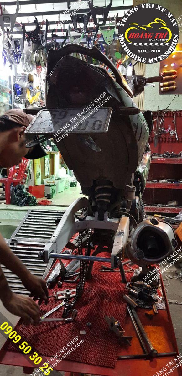 Nhân viên Hoàng Trí Racing Shop đang lắp đặt gấp GP Racing cho Exciter Camo
