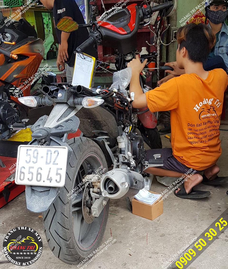 Nhân viên Hoàng Trí Racing Shop đang tháo ổ khóa zin của Exciter 150 2019