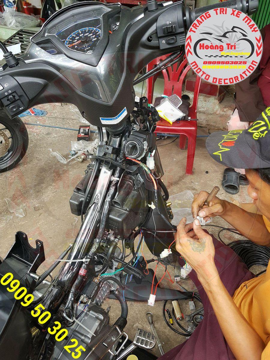 Nhân viên Hoàng Trí Racing Shop đang lắp khóa smartkey cho Jupiter