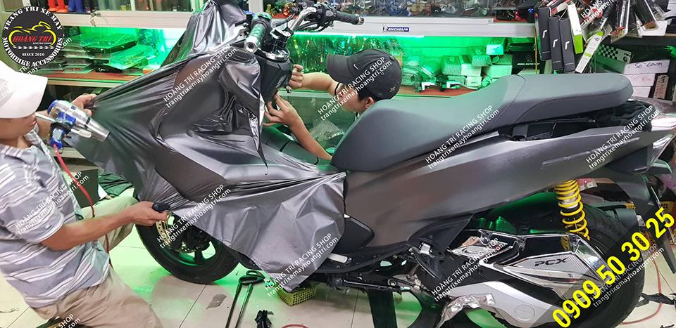 Nhân viên đang thi công dán decal nhôm xước PCX 2018