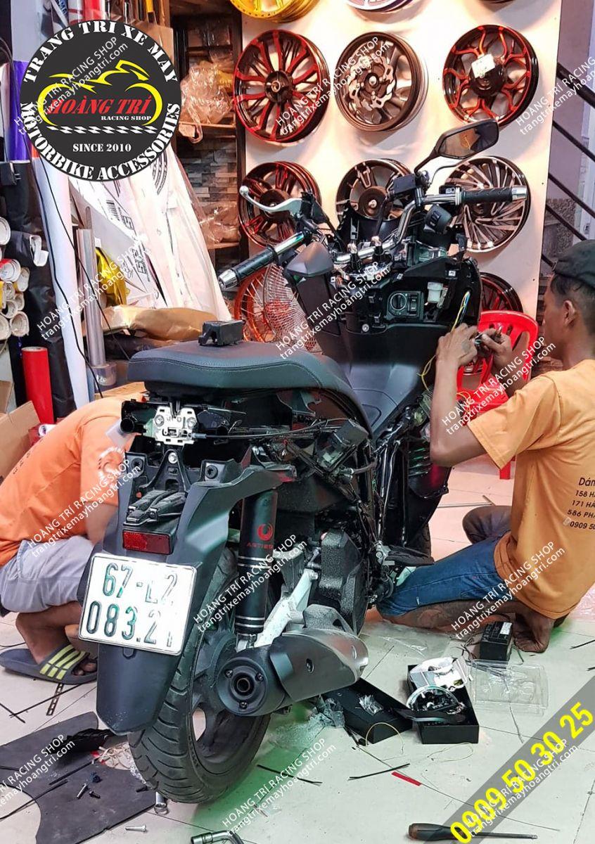 Nhân viên Hoàng Trí Racing Shop đang thi công   lắp đặt đèn bi cầu tăng sáng đèn pha PCX 2018