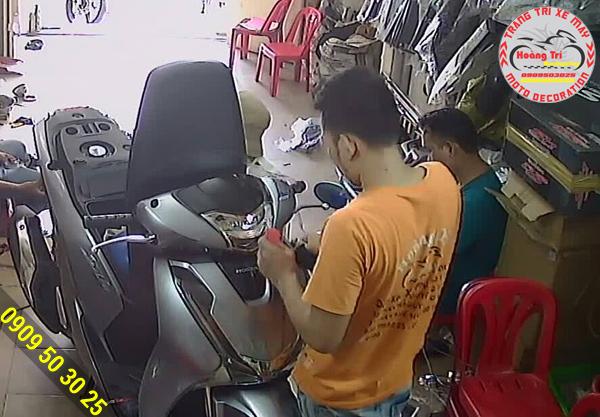 Hình chụp từ Camera, nhân viên Hoàng Trí đang chuẩn bị dán keo xe SH 2017