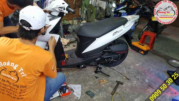 Nhân viên Hoàng Trí Racing Shop đang thi công dán keo xe cho xế Suzuki Address