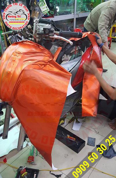 Nhân viên Hoàng Trí Racing Shop đang dán decal nhôm xước tân trang xe cũ cho khách