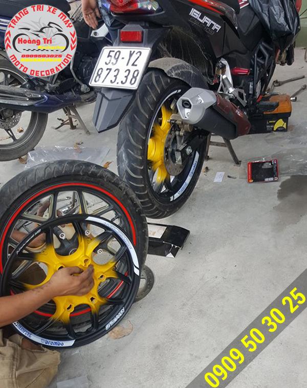 Nhân viên Hoàng Trí Racing Shop đang lắp đặt ốp mâm winner vào mâm xe