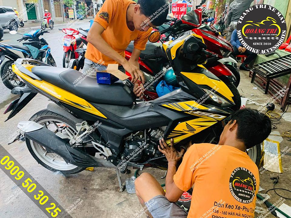 Nhân viên đang lắp đặt khóa smartkey cho chiếc Winner V1 màu vàng